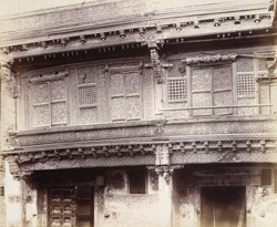 Detail of upper storey of front of a banya's house, Patan, showing elaborate wood carving